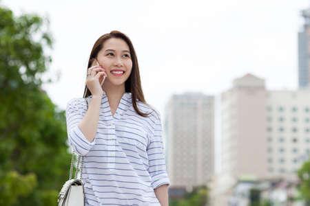 hablando por celular: Mujer asiática del teléfono celular llamada sonrisa lado mirando calle de la ciudad hablando