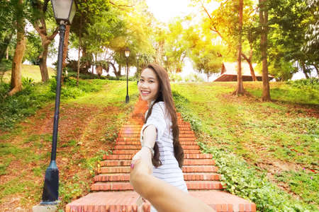follow: Asian woman follow me holding man hand happy smile leads green park, concept welcome to asia Stock Photo