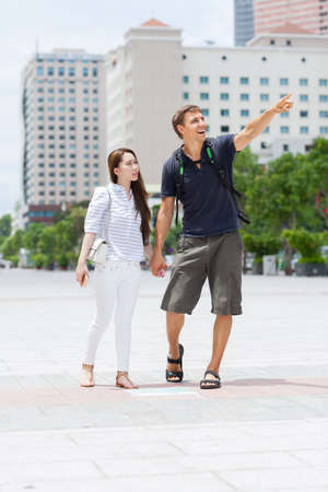 mix race: Couple asian girl and caucasian man tourist smile point finger sightseeing, mix race friends outdoor city street Stock Photo