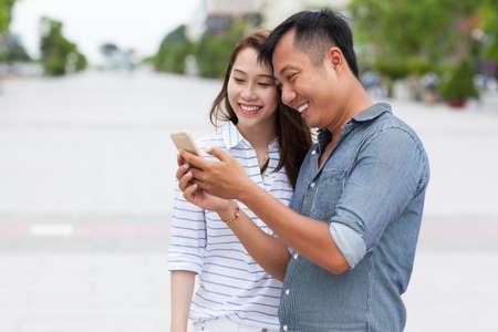 parejas jovenes: Pareja asi�tica utilizando mensaje de tel�fono celular inteligente sonrisa pie en la calle de la ciudad Foto de archivo