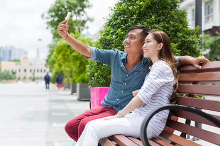 pareja adolescente: Pares asiáticos toma selfie foto retrato sentada banco de la calle de la ciudad al aire libre Foto de archivo