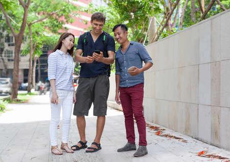 mix race: Asian couple help tourist cell smart phone caucasian man mix race friends outdoor city street