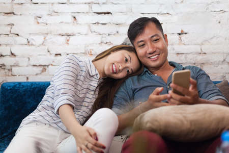 using: Asian couple sitting sofa using cell smart phone happy love smile romantic embrace