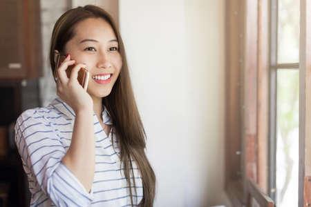 hablando por celular: La mujer asiática llamada de teléfono celular sonrisa hablando cerca de la ventana