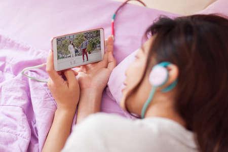 cine: Asiática joven muchacha viendo vídeo móvil auriculares desgaste elegante teléfono acostado en la cama