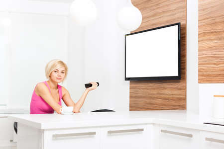 changing channel: woman smile watching tv hold remote control changing channel, young girl in living room at home, isolated screen empty copy space