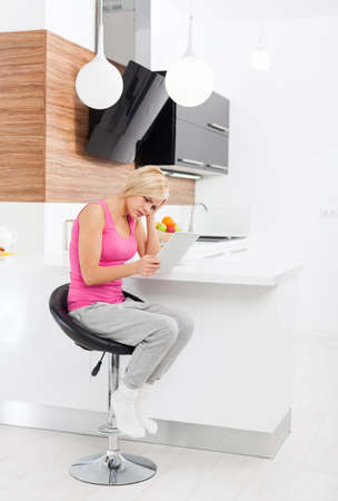negative emotion: upset woman using tablet computer at home unhappy negative emotion, sad girl problem Stock Photo