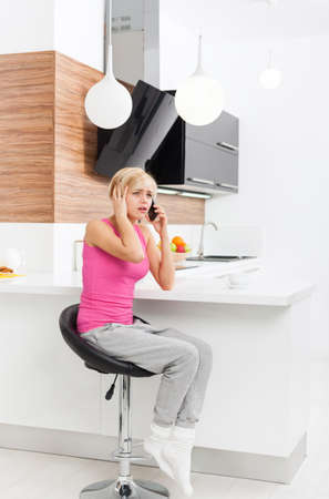 negative emotion: disappointed woman using phone, sad call, sitting table living room, at home indoors, girl negative emotion unhappy talking cellphone, modern bright room Stock Photo