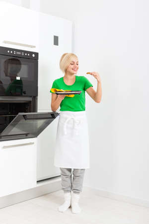 oven tray: woman cooking taste cookies, baking taking from oven tray, young smile girl modern kitchen at home
