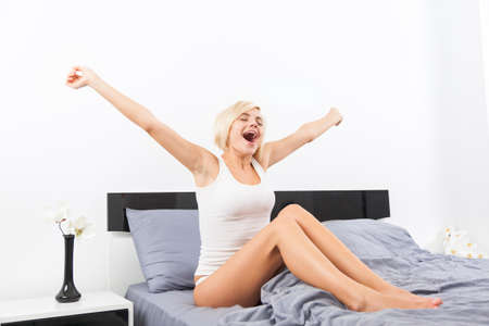 cute woman yawning, morning wake sitting on her bright bed at home, young girl stretching raised arms hands up