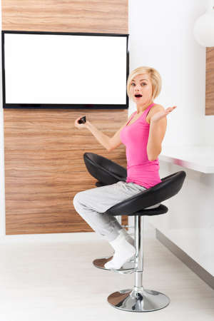 negative area: woman watching tv negative emotion scared, terrified hold remote control changing channel, shock fear girl in living room at home, isolated screen empty copy space