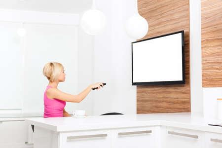 changing channel: woman watching tv hold remote control changing channel, young girl in living room at home, isolated screen empty copy space