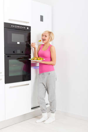 refrigerator kitchen: young smile woman healthy eating vegetable fresh salad, holding fork in hand, pretty girl standing near refrigerator white bright modern kitchen