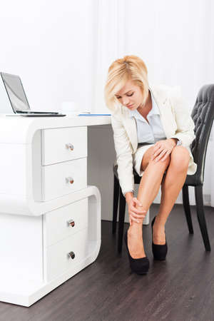 office shoes: business woman feet pain wear high heel new shoes, businesswoman hurt legs formal wear elegant white suit sitting at desk modern bright office Stock Photo
