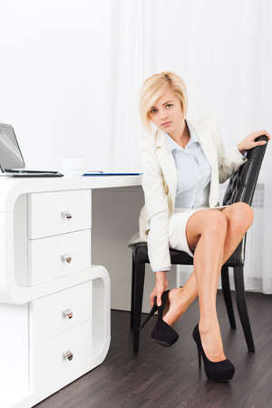 suit skirt: business woman feet pain wear high heel new shoes, businesswoman hurt legs formal wear elegant white suit sitting at desk modern bright office Stock Photo