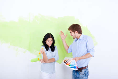 couple arguing: young couple paint wall green brush, at home renovate