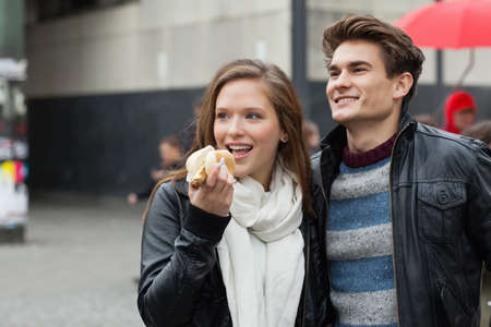 unhealthful: Happy young couple with hot dog looking away outdoors