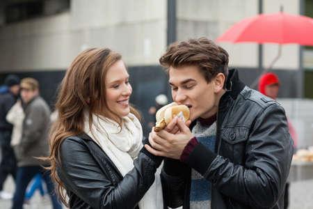 unhealthful: Happy young woman feeding hotdog to man outdoors