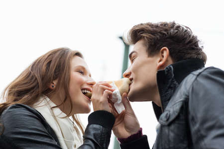 unhealthful: Low angle view of happy young couple eating hotdog together against sky Stock Photo
