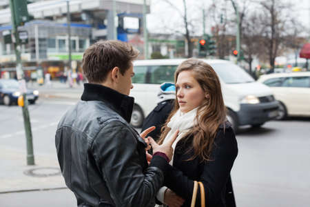 communicating: Young couple in jackets communicating on street side
