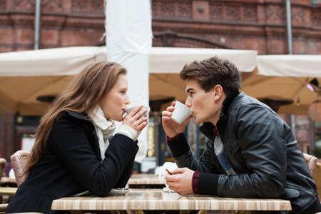 amantes: Vista lateral de la joven pareja, beber café juntos en el restaurante al aire libre