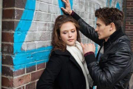 hombre romantico: Romantic man looking at beautiful girlfriend leaning on wall Foto de archivo