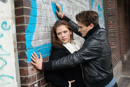 winter woman: Affectionate man looking at beautiful woman leaning on wall Stock Photo