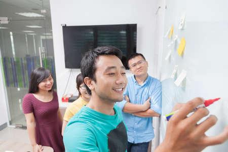 lluvia de ideas: la gente de negocios asiáticas del dibujo en la pizarra pared blanca con las notas adhesivas de oficina de las propiedades creativa