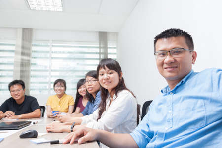 Asian business people team happy smile man face, group businesspeople sitting at desk real office Stockfoto