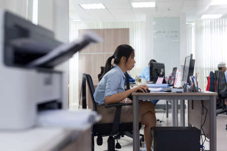 Asian businesswoman working computer sitting office desk busy Stock Photo