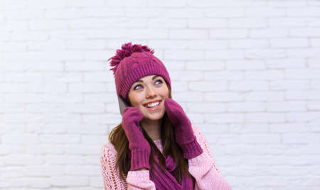 looking aside: Attractive Teenage Girl Cell Phone Call Looking Aside Copy Space Smile Over White Brick Background