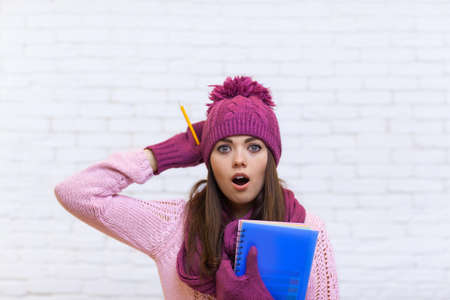 stunned: Attractive Stunned Teenage Girl In Pink Hat Student Shocked Holding Folder Pencil Over White Brick Background