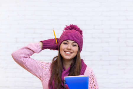 pink hat: Attractive Student Girl Happy Emotional Smile In Pink Hat Holding Folder Pencil Over White Brick Background Stock Photo