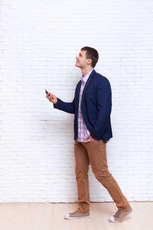 Mann mit Business-Handy Smartphone Gehen Look Up Raum Social Network Communication Ganzkörperansicht über Weiß Ziegelmauer Zum Kopieren Standard-Bild