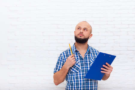 businessman pondering documents: Serious Casual Bearded Business Man Holding Folder Look To Copy Space Pondering Doubtful Office Over White Brick Wall
