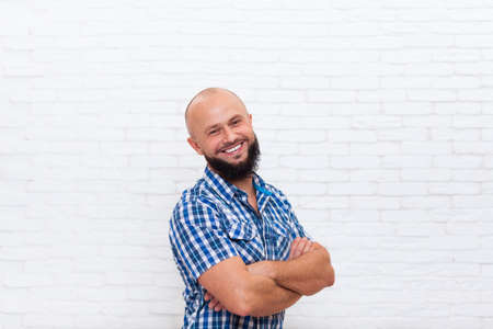 adult wall: Casual Bearded Business Man Smiling Folded Hands Office Over White Brick Wall Stock Photo