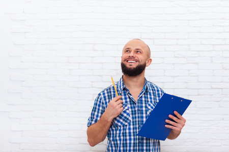 pencil point: Casual Bearded Business Man Holding Folder Pencil Point Look Up To Copy Space Office Over White Brick Wall