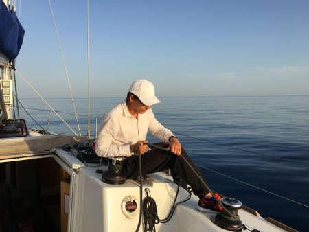 yachtsman: Young man sailing yacht yachtsman holding hands rope vacation sail holidays people travel