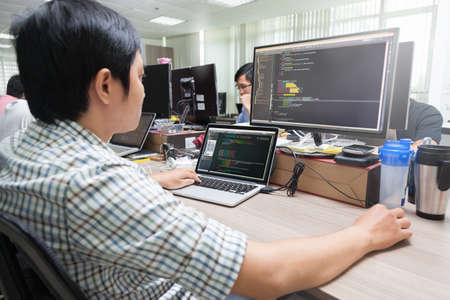 software company: Asian Outsource Software Developer Looking Screen Sitting At Desk Working Laptop Computer Mobile Application Software Real Office