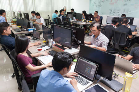 software company: Asian Software Developers Business People Sitting Desk Working Laptop Computer Businesspeople Team Real Office Stock Photo