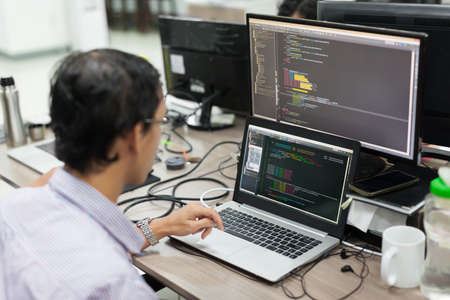 Asian Outsource Software Developer Looking Screen Sitting At Desk Working Laptop Computer Mobile Application Software Real Office