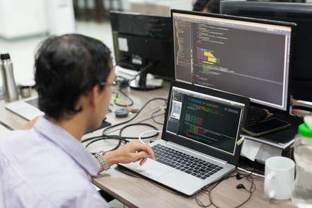 Empresa de trabajo Desarrollador de Software de Asia mirando la pantalla del ordenador portátil sentado en el escritorio de trabajo de Programas informáticos de aplicaciones móviles de oficina real