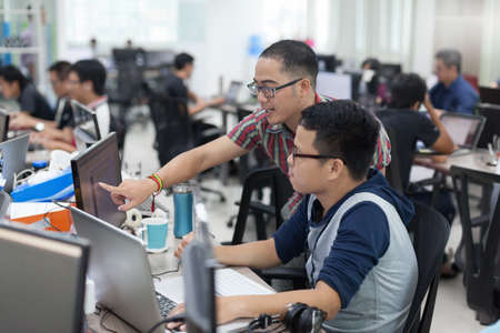Asian Colleagues Software Developers Team Sitting At Desk Working Laptop Computer Business People Group Real Office 写真素材