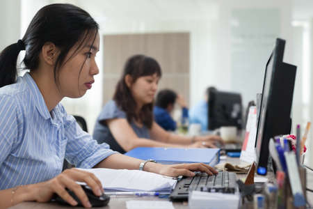 Asian businesswomen working computer sitting office desk busy 写真素材