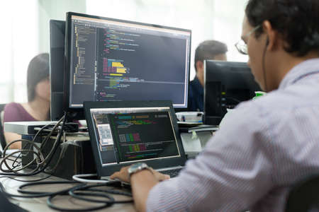 Asian Outsource Developer Looking Screen Sitting At Desk Working Laptop Computer Mobile Application Software Real Office 스톡 콘텐츠
