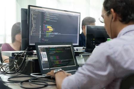 Empresa de trabajo asiático desarrollador mirando la pantalla del ordenador portátil sentado en el escritorio de trabajo de Programas informáticos de aplicaciones móviles de oficina real