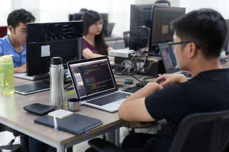 Empresa de trabajo asiático desarrollador del equipo sentado en el escritorio del ordenador portátil de trabajo de Programas informáticos de aplicaciones móviles de oficina real