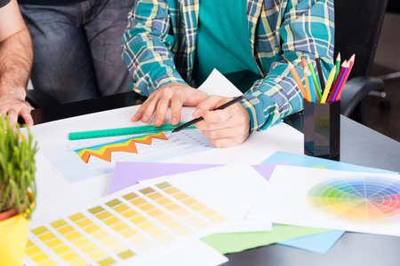 Graphic designer choosing color chart from the colorful sampler creative desk Reklamní fotografie