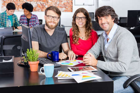 mix race: People office diverse mix race group businesspeople designers working sitting desk smile looking camera casual wear