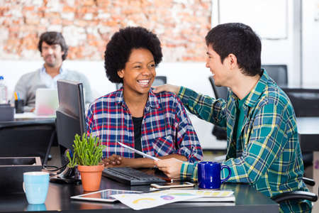 african business man: Two colleagues african american woman asian man diverse mix race talking discussing sitting office desk business people working casual wear